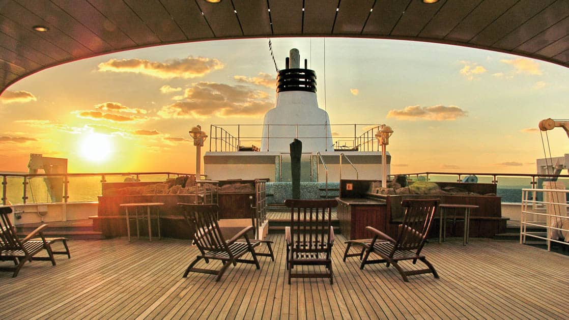 Upper Deck with lounge chairs facing sunset aboard National Geographic Orion expedition ship