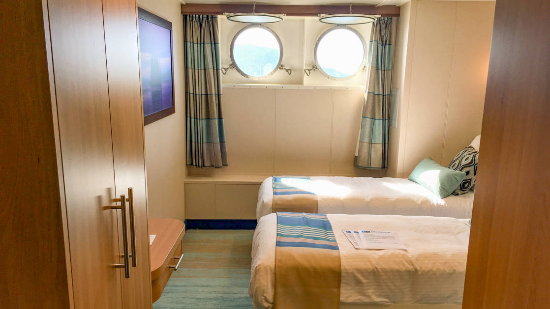 two beds, desk and two portholes in Category 1 cabin aboard National Geographic Quest luxury expedition ship