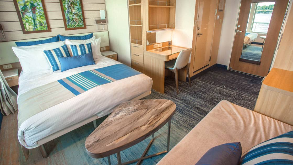 Large bed, sofa, coffee table, small desk and chair in Category 5 cabin aboard National Geographic Quest luxury expedition ship