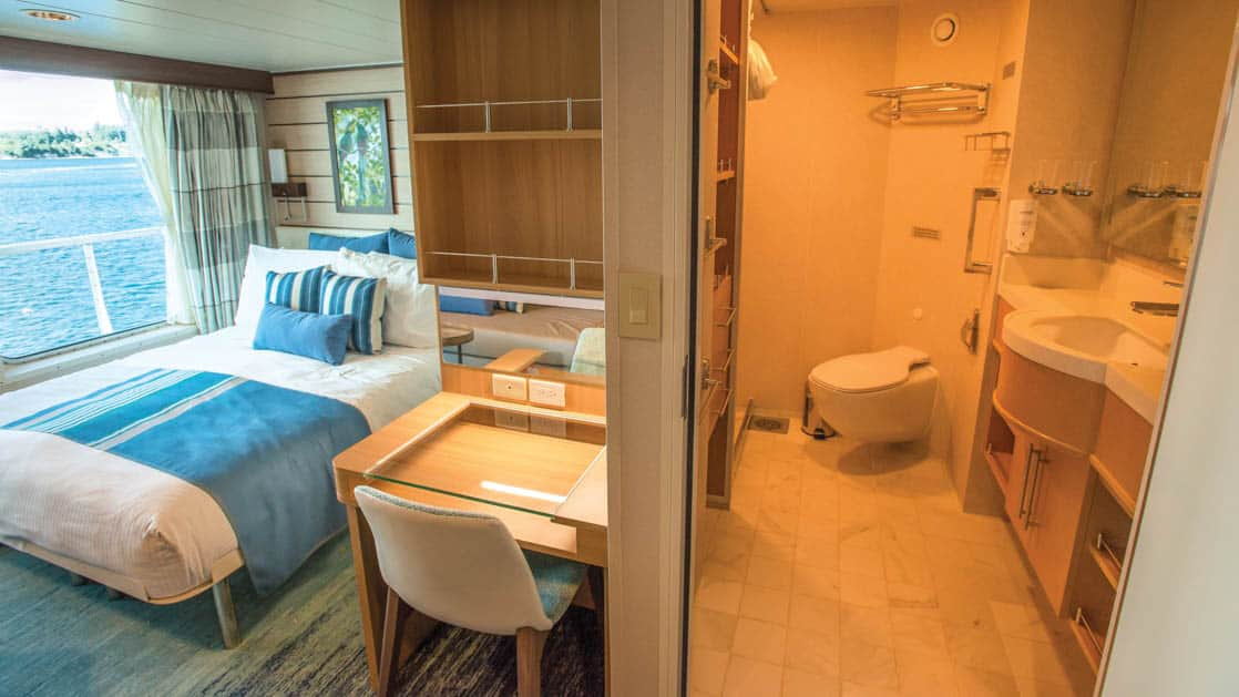 Category 5 cabin with large bed, desk, chair, large windows and bathroom with toilet, shower, sink and mirror aboard National Geographic Quest luxury expedition ship