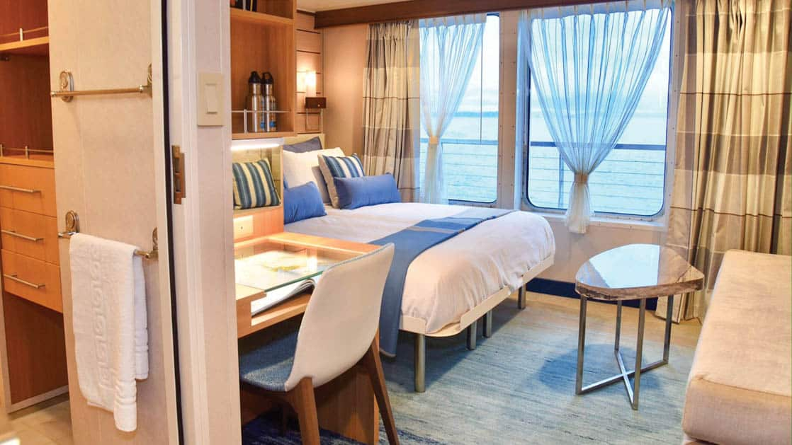 Category 5 suite with large bed, sofa, coffee table, desk, chair and large windows aboard National Geographic Quest luxury expedition ship