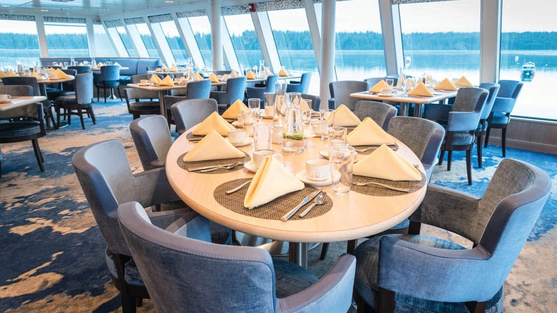 Dining room with elegant table setting and window-lined walls aboard National Geographic Quest luxury expedition ship