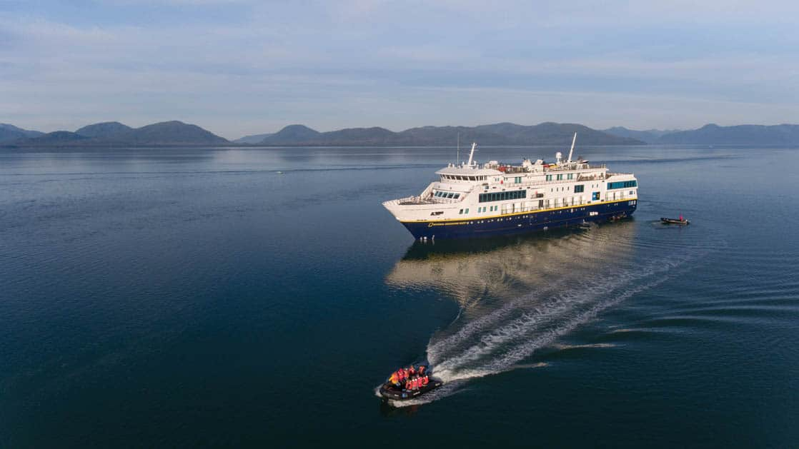 Aerial of zodiac vessel loaded with passengers for shore excursion with full exterior of port side of National Geographic Quest luxury expedition ship