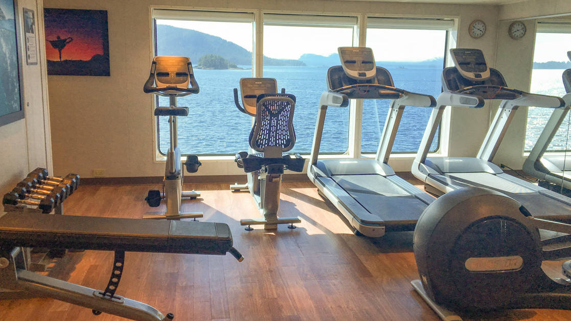 Free weights and exercise machines in front of large windows in gym aboard National Geographic Quest luxury expedition ship