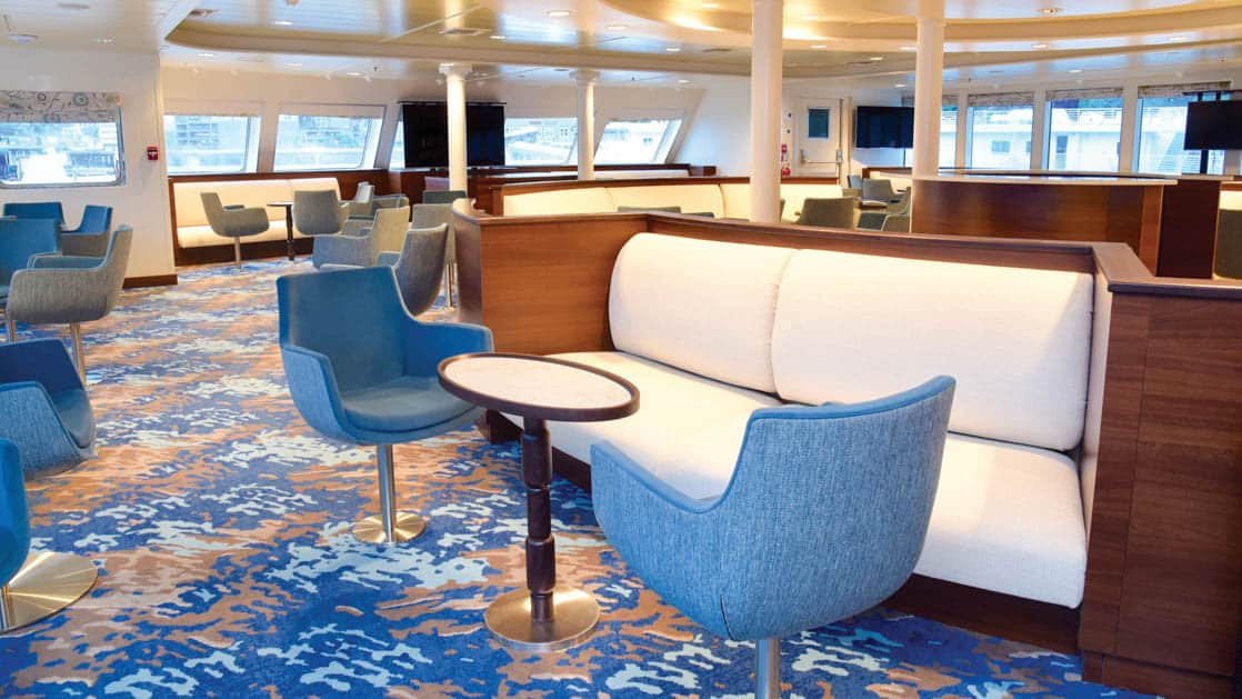 Lounge with booths, tables and chairs with window-lined walls aboard National Geographic Quest luxury expedition ship