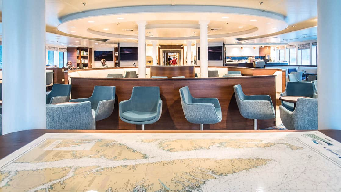 Large map set up on table in lounge area with chairs and tables aboard National Geographic Quest luxury expedition ship