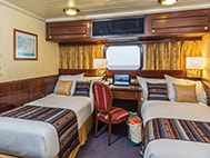 Thumbnail of cabin interior with two beds, desk, chair and window aboard National Geographic Islander expedition ship in the Galapagos Islands