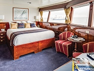 category 5 cabin aboard national geographic islander galapagos small ship with large bed, table and chairs, large windows and a picture above the bed