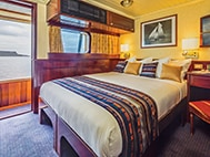 Thumbnail of cabin interior with large bed, window and glassed-in terrace aboard National Geographic Islander expedition ship in the Galapagos Islands