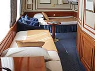 Thumbnail of cabin with two beds, two large windows, two armchairs and small table aboard National Geographic Orion expedition ship