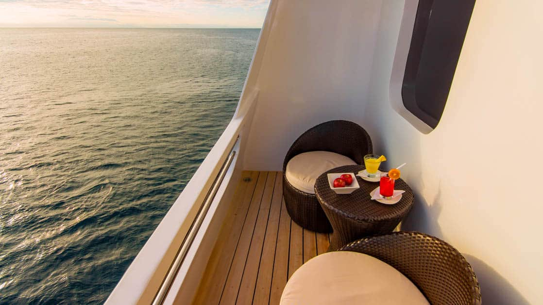 Upper Deck Suite balcony with small table and 2 chairs aboard Natural Paradise Galapagos small ship