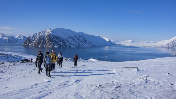 group of explorers hikes on glacier during excursion from north norway aurora borealis whales cruise