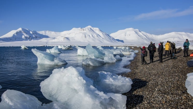 hikers in north norway, large ice chunks on coast near group of hikers