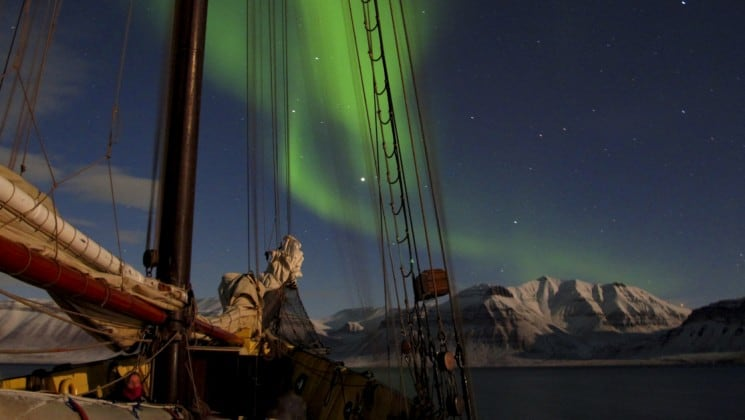 northern lights above docked ship in north norway on small ship cruise
