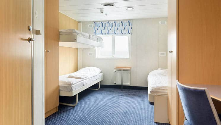 Triple cabin aboard Ocean Nova with 3 beds, a stool, window and cabinet