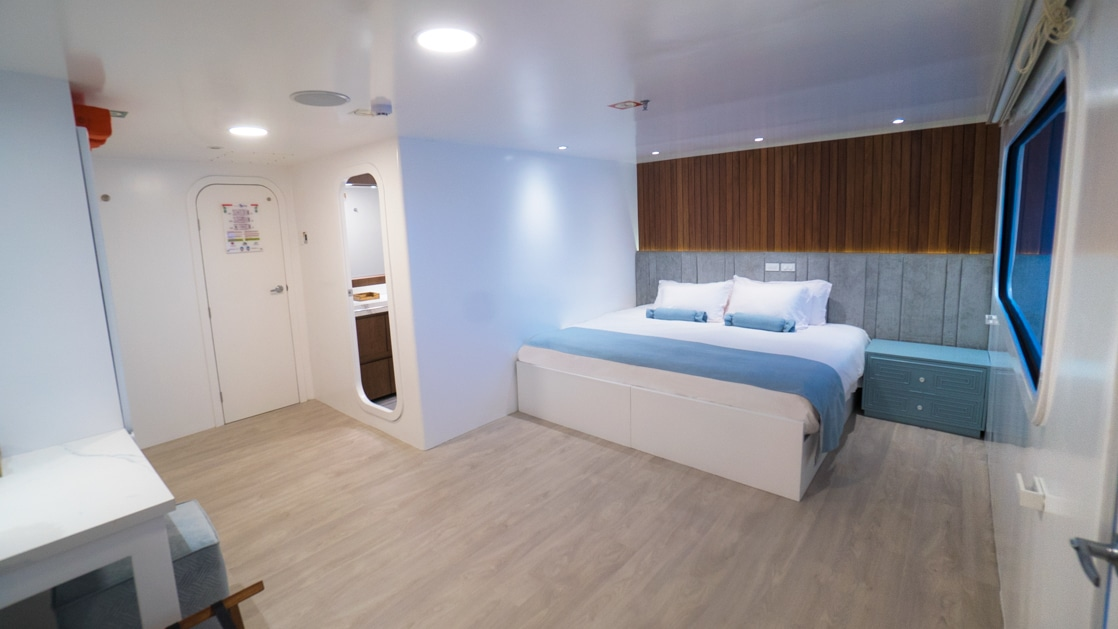 Large cabin with white walls, wooden accents & king-size bed covered in white & blue linens aboard catamaran Ocean Spray.