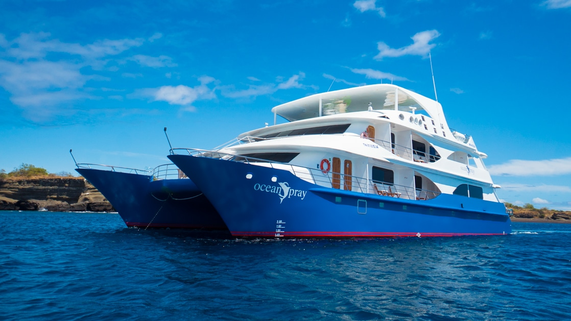 Small catamaran Ocean Spray with blue hull & white upper decks sits in calm water on a sunny day in Galapagos.
