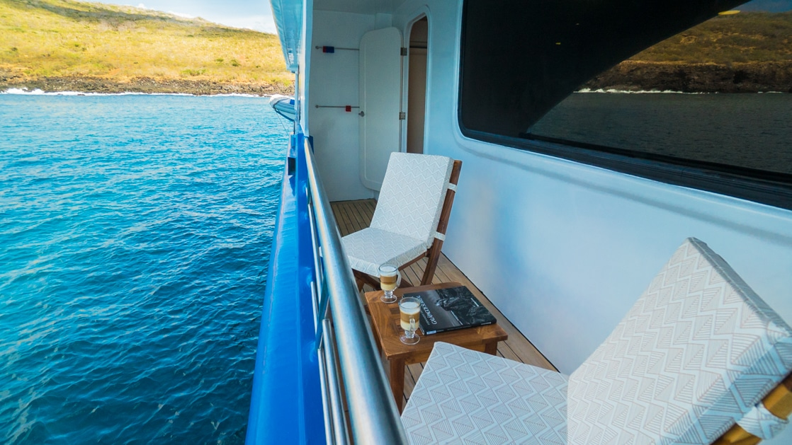 Narrow private balcony with 2 padded wooden chairs & wood coffee table on a ship sitting in calm water on a sunny day.