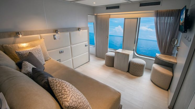 2-Bedroom Suite aboard Origin, Theory & Evolve luxury Galapagos yachts, with adjoining room showing beige couch with many pillows, floor-length windows, flatscreen TV & natural decor.