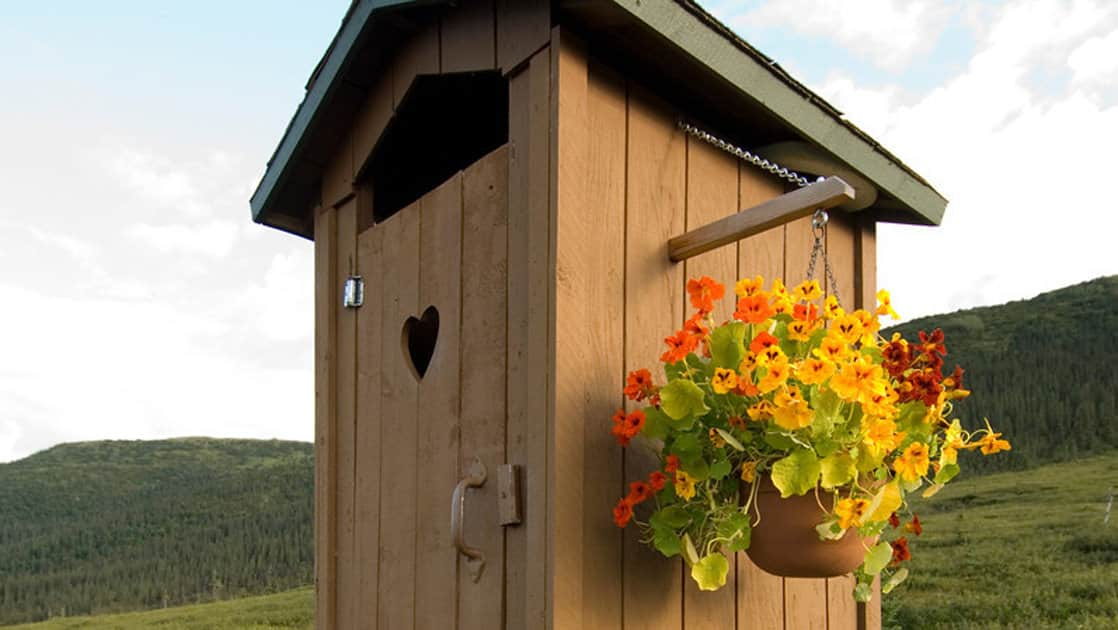 One of the charming and meticulously maintained outhouses at the rugged, yet comfortable Camp Denali, in Alaska, with a basket of flowers hanging outside.