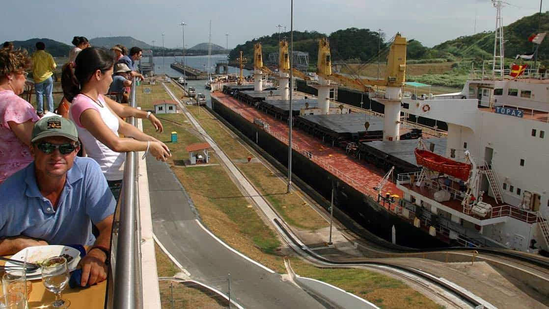 adventure travelers relax and watch small ships travel through the miraflores locks during the Panama Discovery land tour