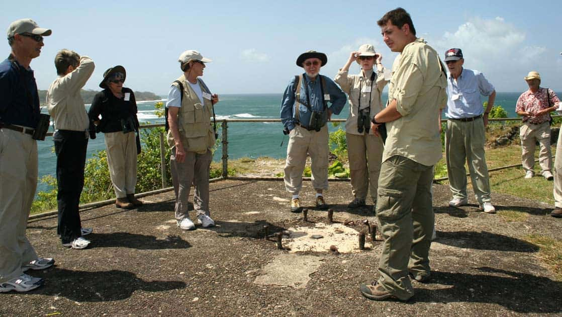 travelers listen to a guide on the trans isthmian route overlooking the ocean on a sunny day