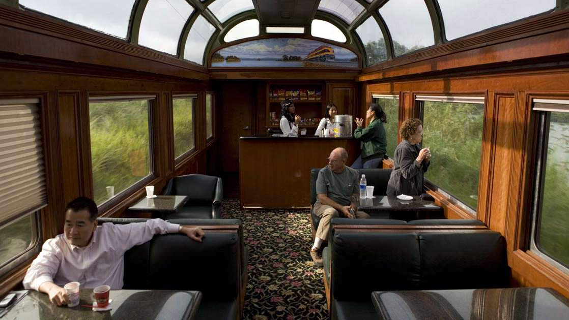travelers on a luxury passenger train with windows and a glass ceiling on the panama discovery land tour relax on large comfortable chairs and tables