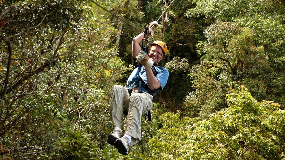 a traveler goes on a zip line with the jungle canopy below him on the panama adventure land tour