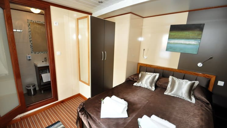 large bed with pillows and towels on it in a cabin aboard the president mediterranean luxury yacht