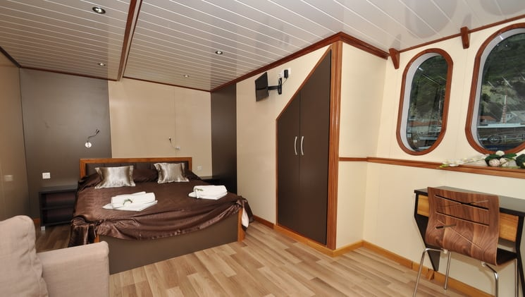 a cabin with wood floors, a bed and an angular door aboard the president mediterranean luxury yacht