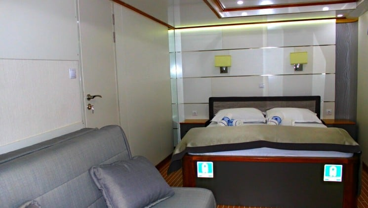 a large bed and sofa in a muted-tone room aboard the prestige luxury yacht in the mediterranean
