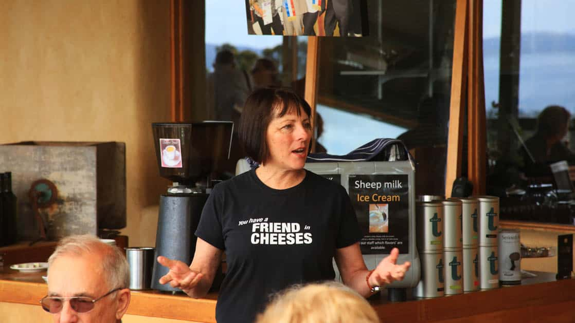 a guide wearing a black shirt reading 'you have a friend in cheese' talks to a group of small ship passengers during a stop on the pristine tasmania cruise trip