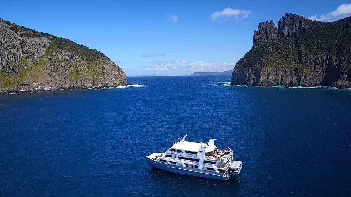 the coral discoverer small ship sits atop azure water in tasmania australia on a sunny day with cliffs on either side nearly coming together in the distance