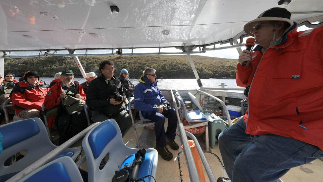 a guide in a red jacket speaks into a microphone on a boat to australia small ship passengers who intently listen
