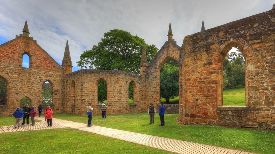 people stand on the grass in front of the stone walls of port arthur in australia on a cloudy day