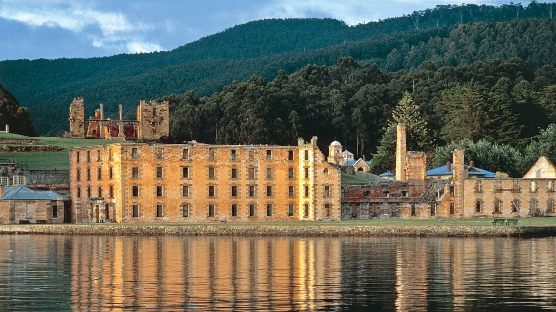 port arthur historic site in australia illuminated by the sun with calm waters in front of it and lush forests behind it