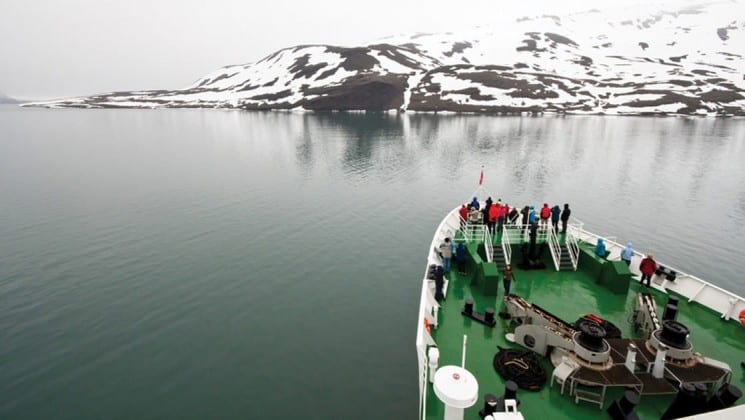 passengers at bow of small cruise ship in arctic waters