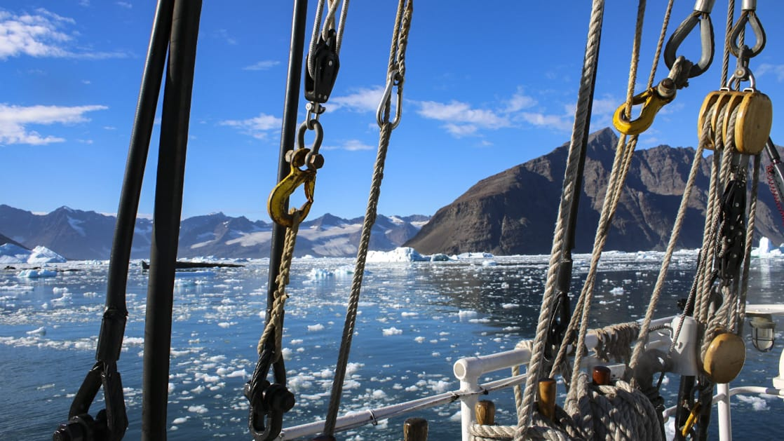 ropes and pulleys aboard the Rembrandt van Rijn arctic small ship with arctic sea ice and land in the background