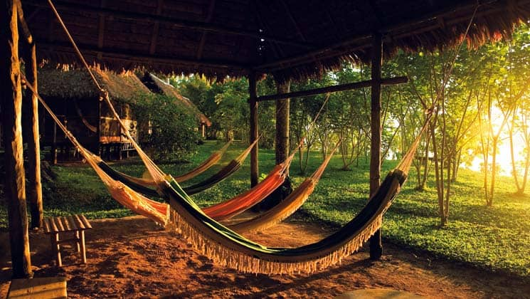 Guests can relax and watch the waning sunlight filter through the Amazon forest while sitting in a hammock under the covered porch at Inkaterra Reserva Amazonic, an eco-luxury lodge in Peru.