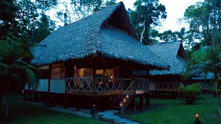 The exterior of a hut at Inkaterra Reserva Amazonica with a thatched roof and covered patio. The eco-luxury lodge has four cabana options, with authentic, tall fishtail palm rooftops and indigenous architectural design.