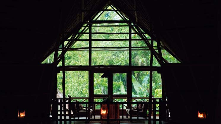 The view from inside a hut at Inkaterra Reserva Amazonica, with indigenous architectural design, looks over lush jungle near Peru's Tambopata National Park.