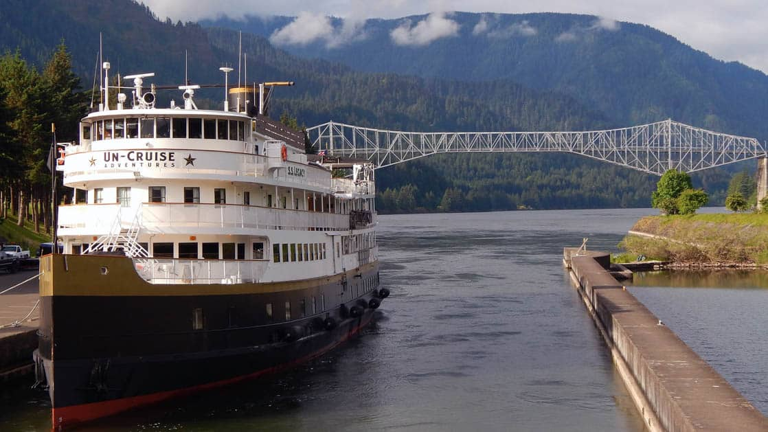 Wilderness legacy small ship anchored at a dock in the pacific northwest with a bridge and mountains behind it during the Rivers of Adventure & Wine Cruise