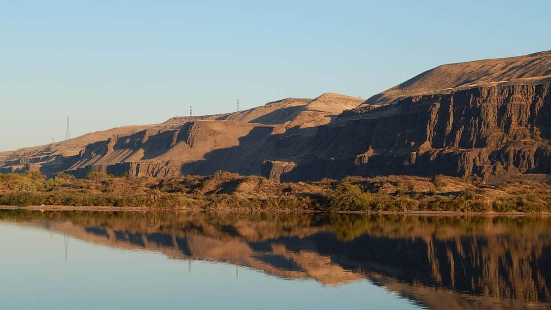 the columbia river on a calm sunny day with large cliffs on the side seen from the s.s. legacy small ship on the Rivers of Wine & Culinary pacific northwest cruise