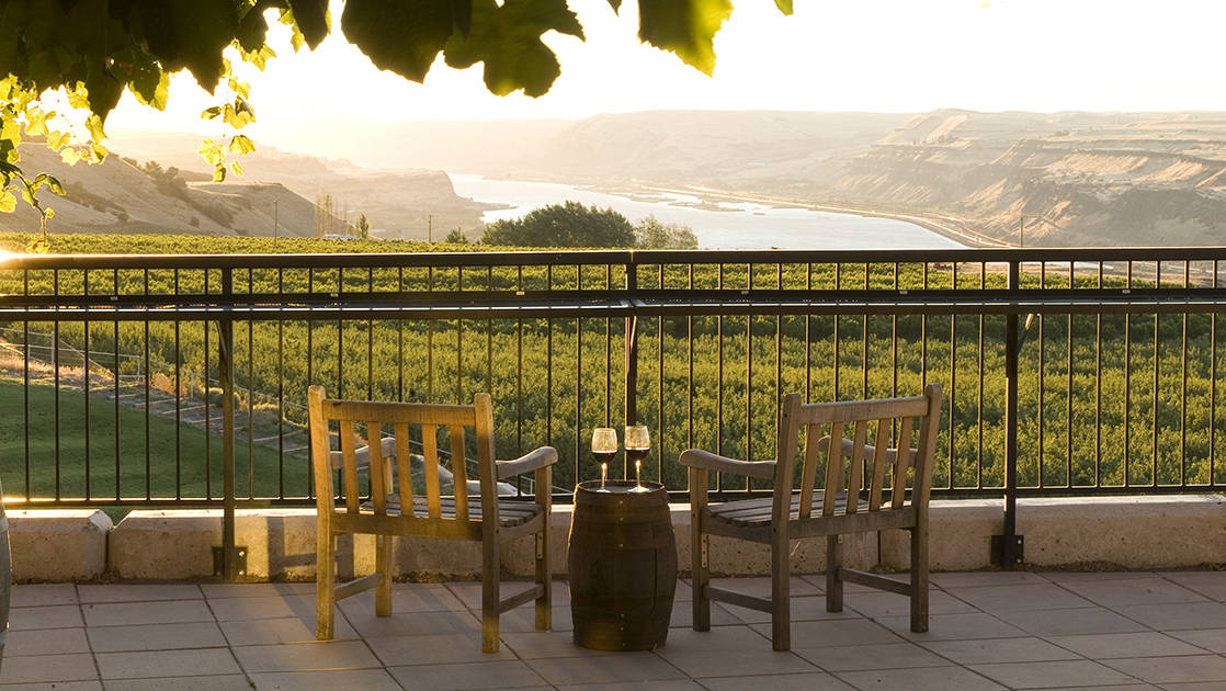 2 chairs with a barrel and two glasses of wine look over a vineyard with the columbia river, pacific northwest in the background
