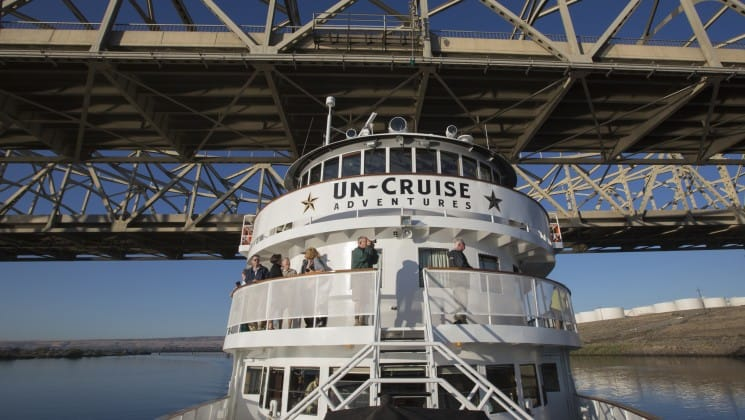 adventure travelers taking pictures on the front of the ss legacy small ship while it goes under a bridge during the rivers of wine & culinary cruise in the pacific northwest