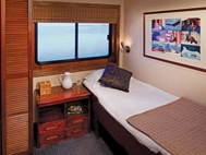 Safari Voyager panama small ship single cabin with bed, picture above the bed and 2 windows