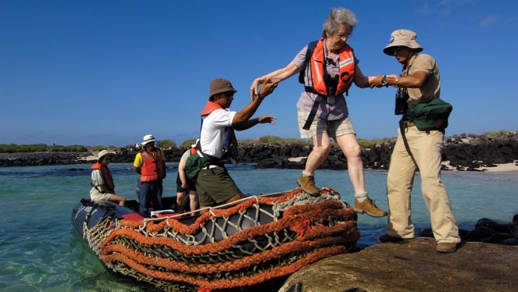 guide helping guests off small vessel for dry landing in galapagos islands