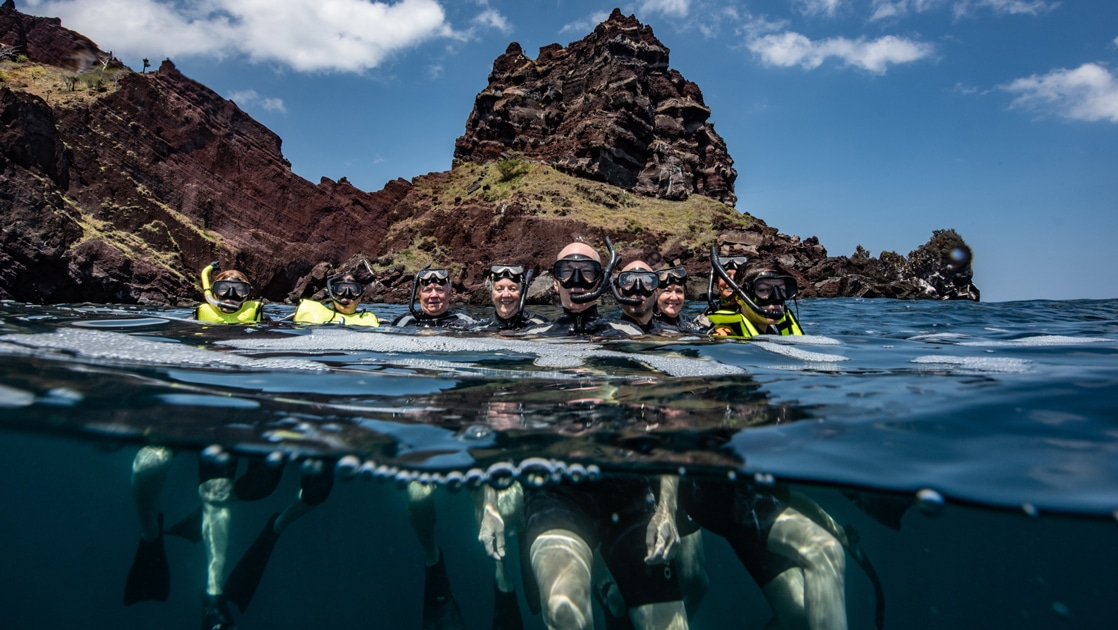 A partially underwater photo of a group of snorkelers floating at the surface of the water in the Galapagos islands.