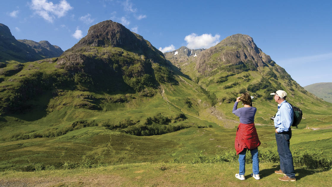 Man and woman admiring the view and taking a picture of the green mountains in Scotland