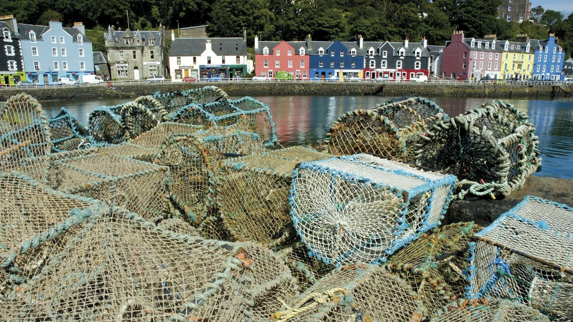 Colorful houses and buildings along the waterfront in scotland with fishing traps and gear in the foreground on the dock